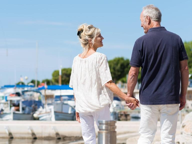 couple holding hands walking down a dock